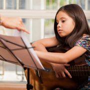 Menina tendo aula de guitarra