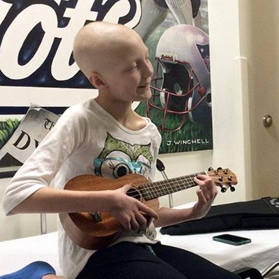 Criança com cavaquinho em Oncologia