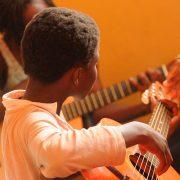 Criança com autismo dedilhando guitarra, créditos Pixabay
