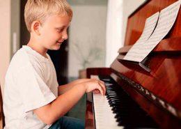 Criança feliz a tocar piano
